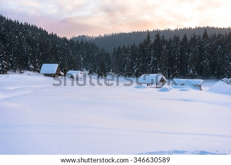 Snow-covered winter mountain landscape with abandoned wooden huts at sunset - stock photo