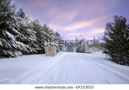 Snow covered winter road through a state park in Michigan - stock photo