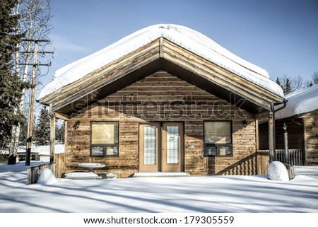 Snow covered wood cabin between the trees in winter - stock photo
