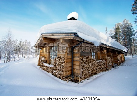 Snow-covered wooden house in forest, with a log fire for winter and plenty of fuel - stock photo