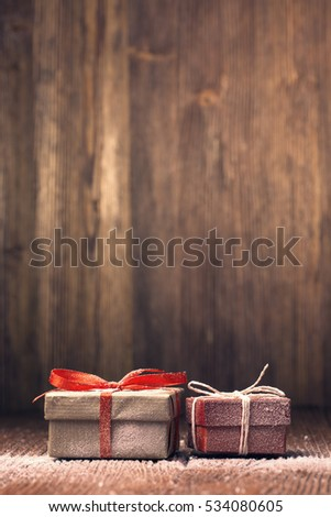 Snow-covered Xmas gift boxes against wooden background
