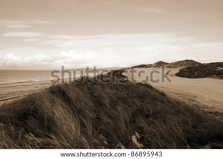 snow covering on a golf course in ireland in winter with sea and cliffs in background in sepia - stock photo