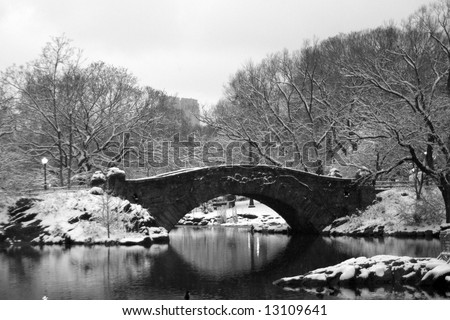 Snow covers a stone bridge over a pond in Central Park