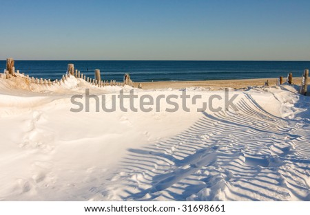 Snow covers part of the beach at the Jersey Shore. - stock photo