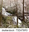 Snow covers the leaves and mountain as Laurel falls cascades over the mountain and lone hiker stands on bridge - stock photo