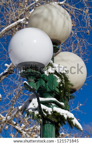 Snow decorates a lamp post in Santa Fe's historic Plaza - stock photo