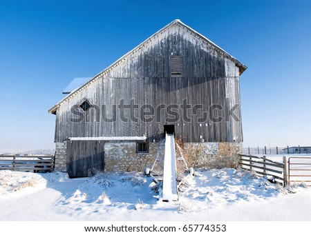 Snow drapes an old barn and farm equipment against a cold blue sky. - stock photo