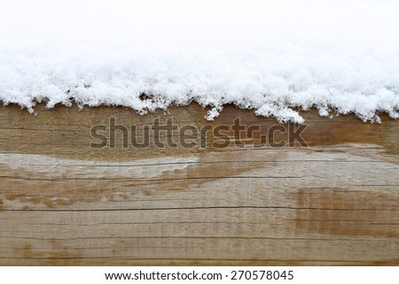 Snow drift on a wood texture with blank space or room for copy, text, or your words. Horizontal with warm tones. - stock photo