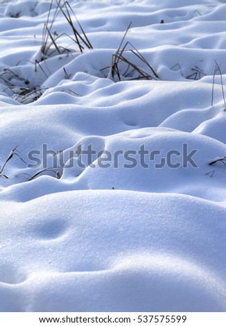 Snow drifts in snowbound winter meadow after snowfall