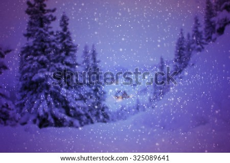 Snow falling against winter landscape - focused on snowflakes - stock photo