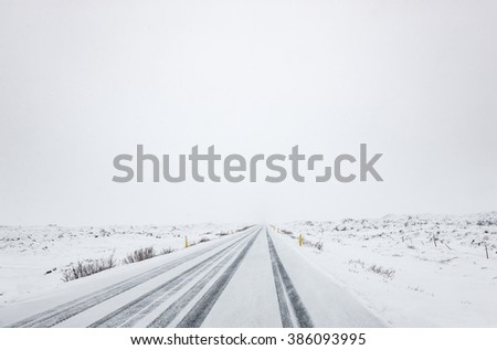 Snow falling on a country road in iceland in the winter - stock photo