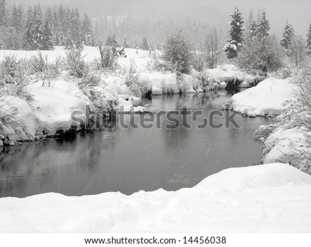 Snow falling on a river with snowy banks in Whistler British Columbia - stock photo