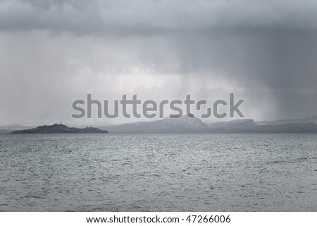 Snow falling over Arthur's Seat and Inchkeith looking over the Firth of Forth from Fife