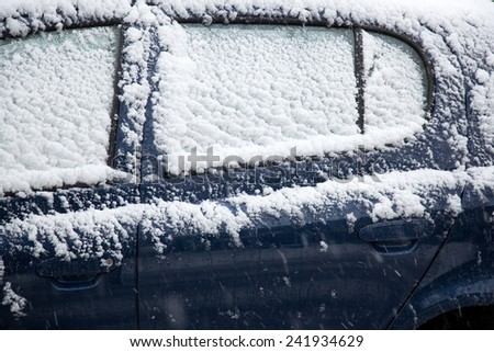 snow fals on door and windshields of blue car - stock photo
