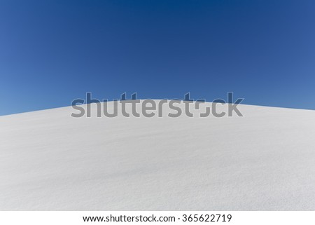 Snow field with blue sky and text space - stock photo