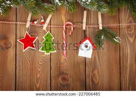 Snow fir tree and christmas decor on rope over rustic wooden board with copy space - stock photo