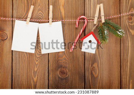 Snow fir tree, photo frame and christmas decor on rope over rustic wooden board with copy space - stock photo