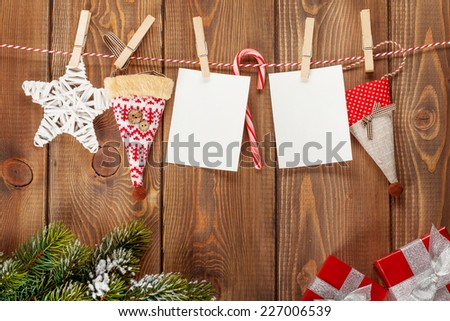 Snow fir tree, photo frames and christmas decor on rope over rustic wooden board with copy space - stock photo