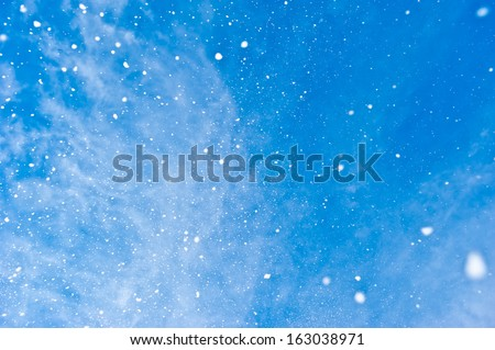 Snow flakes falling from clear blue sky - stock photo