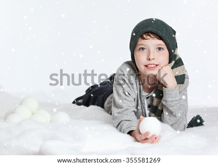 Snow fun.  Adorable young boy lying in the 'snow' and holding a 'snowball'.   - stock photo