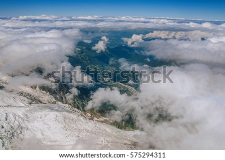 Snow, glacier and Chamonix Valley in a sunny day, viewed from the Aiguille du Midi, near Chamonix. A famous ski resort located in Haute-Savoie Province, at the foot of Mont Blanc in the French Alps.
