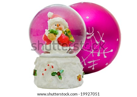 Snow globe - Christmas souvenir against one pink ball, isolated on white background - stock photo