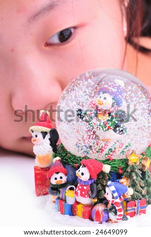 snow globe-focus is on the snow globe and the girl who is slightly out of focus is watching it - stock photo