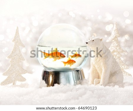 Snow globe with fish in magical winter scene - stock photo