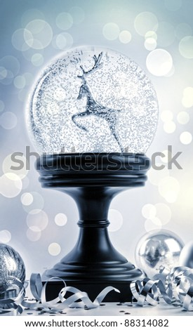 Snow globe with ornaments against a festive background - stock photo