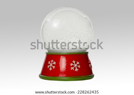 Snow globe with show inside, on a red base, isolated on white background