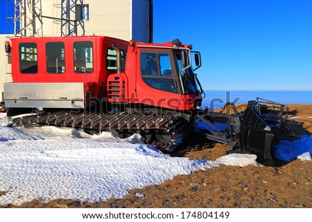 Snow grooming machine stopped due to lack of snow - stock photo