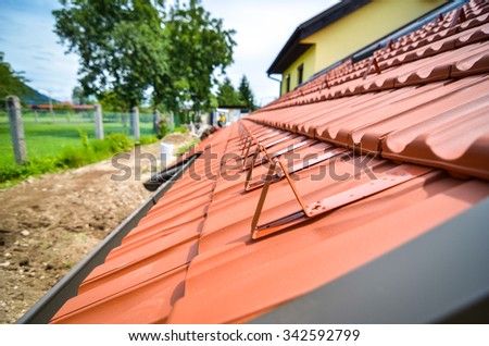 Snow guards on new roof with red orange tiles and drain pipes. tiles. Snowguards installation for traditional roofing. - stock photo