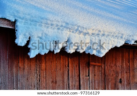 Snow hangs from a roof on a very cold winter day - stock photo