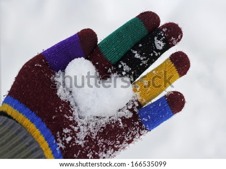 Snow heart in a hand with colorful gloves - stock photo