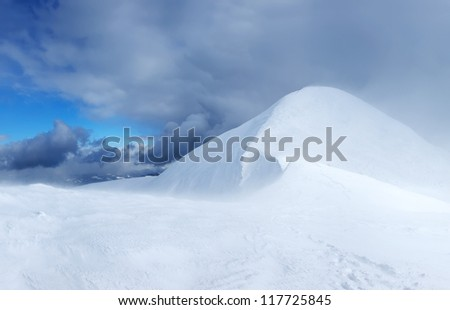 Snow hills and bright sky during storm. - stock photo