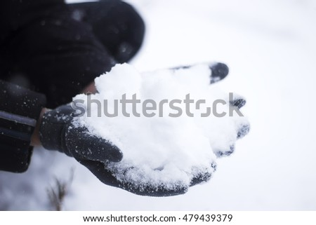 Snow in the man's hands in gloves, selective focus