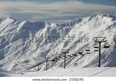 snow landscape with cableway, early morning - stock photo