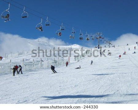 snow landscape with people skiing and a cableway