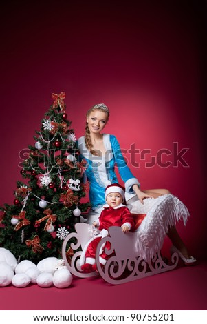Snow Maiden and baby santa claus portrait - stock photo