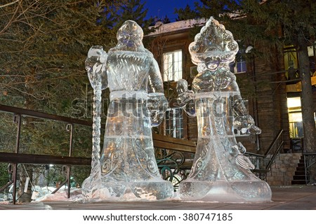 Snow maiden and Santa claus grandfather - Ice figures at night, in the street of Irkutsk, Siberia, Russia. Yhe pure ice is from Baikal lake. - stock photo
