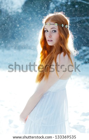 Snow Maiden. Fantasy image of beautiful red head woman standing in snow, looking at camera - stock photo