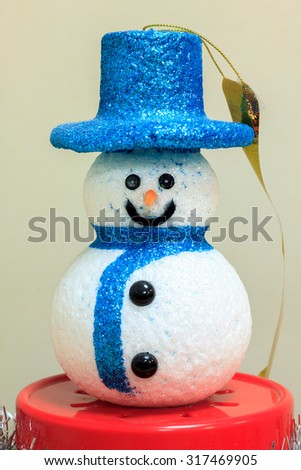 Snow man doll on red base and blur background. - stock photo