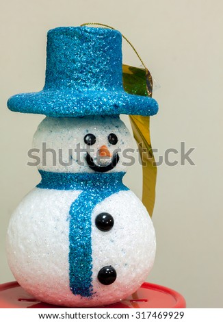 Snow man doll on red base and blur background.