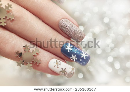 Snow manicure on colored nail Polish with silver snowflakes on a brilliant background. - stock photo