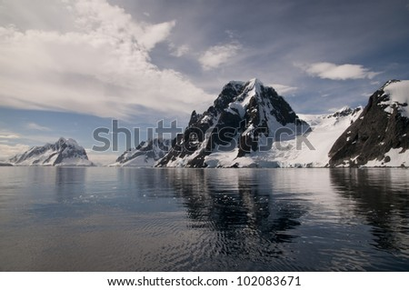 Snow mountain and its reflection in Antarctica - stock photo