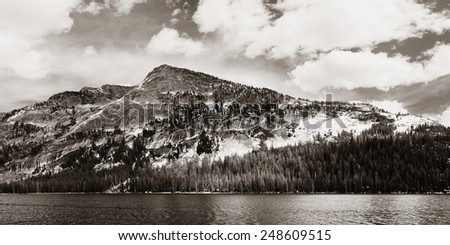 Snow mountain cloud and lake panorama with reflections in Yosemite BW. - stock photo