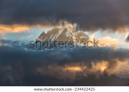 Snow mountain partly obscured by clouds - during sunset (Fishtail Mountain in Nepal)  - stock photo