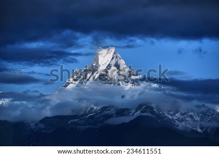 Snow mountain partly obscured by clouds (Fishtail Mountain in Nepal) - stock photo