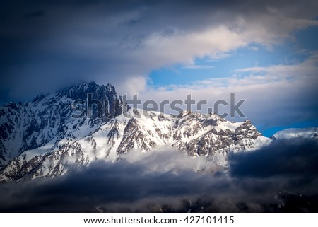 Snow mountain revealing itself behind the dense cloud and fog when the sun light shine on it. Annapurna Conservation Area, Muktinath, Nepal - stock photo