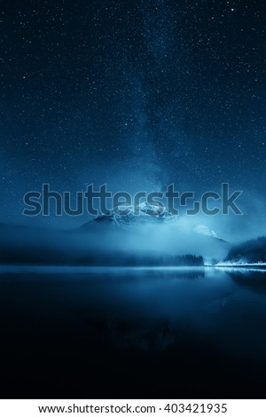Snow mountain with fog over lake with milky way - stock photo